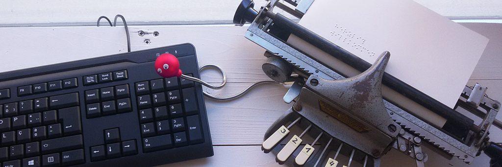 Eine Computer-Tastatur liegt nah bei einer Braille-Schreibmaschine. Ein metallischer Ringel-Wurm mit rotem Kopf verbindet die beiden Geräte miteinander.