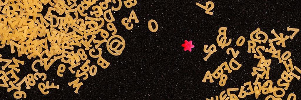 Ein himbeerfarbenes Sternchen liegt inmitten von gelben Buchstaben-Nudeln.